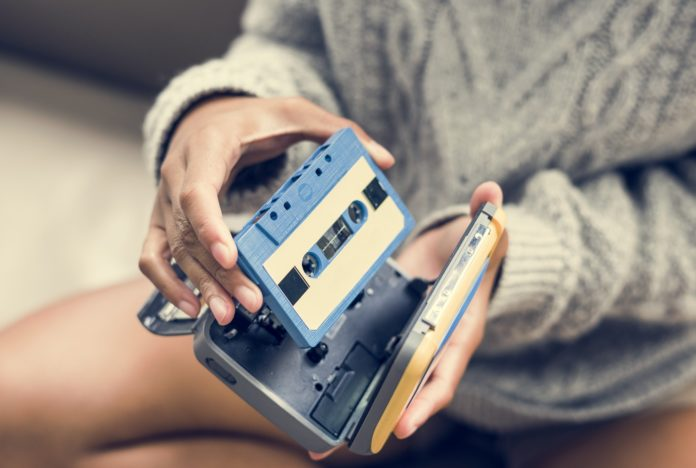 Woman putting a cassette in a cassette player